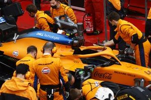 Mechanics work on the car of Lando Norris, McLaren MCL35M