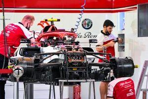 Alfa Romeo mechanics work on one of their cars in the garage