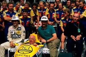 BBC TV commentator Murray Walker in the Williams FW11 sits with the regular drivers Nelson Piquet and Nigel Mansell. Team Owner Frank Williams sits to the right.