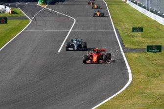 Charles Leclerc, Ferrari SF90, precede Lewis Hamilton, Mercedes AMG F1 W10, sollevando scintille per l'ala danneggiata