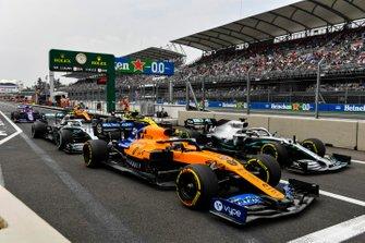 Carlos Sainz Jr., McLaren MCL34, Lewis Hamilton, Mercedes AMG F1 W10, Valtteri Bottas, Mercedes AMG W10, Nico Hulkenberg, Renault F1 Team R.S. 19, Daniil Kvyat, Toro Rosso STR14, et Lando Norris, McLaren MCL34, à la sortie des stands
