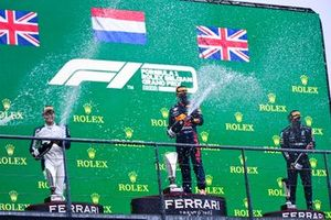George Russell, Williams, 2nd position, Max Verstappen, Red Bull Racing, 1st position, and Lewis Hamilton, Mercedes, 3rd position, spray Champagne on the podium