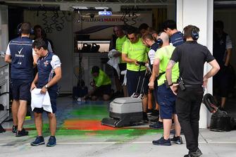 Un meccanico Williams rimuove la vernice aerodinamica dal pavimento del garage