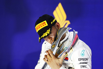 Lewis Hamilton, Mercedes AMG F1, kisses his trophy on the podium as he celebrates after winning the race