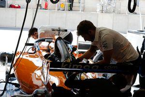 McLaren engineers work on the car of Fernando Alonso, McLaren MCL33, in the garage