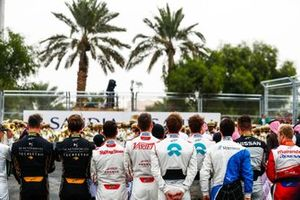 The drivers line up on the grid for the national anthem