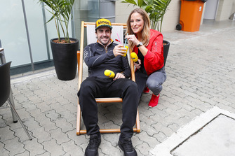 Fernando Alonso, McLaren, holds a drink while sitting on a deckchair next to a RTL presenter