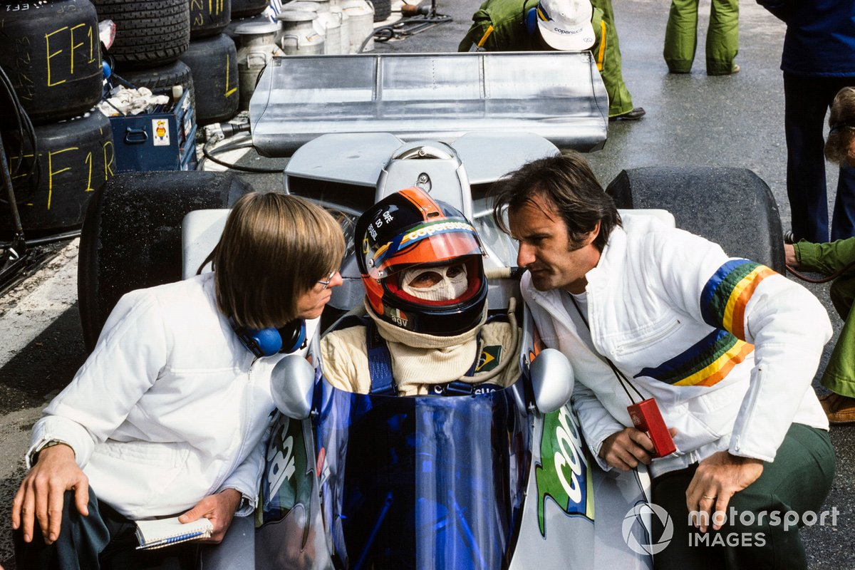 Emerson Fittipaldi talking to his brother Wilson in the pits, and designer Ricardo 'Richard' Divila