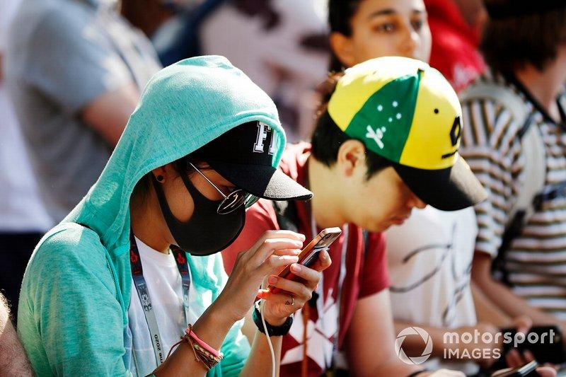 I fan indossano le mascherine protettive in risposta alla pandemia da Coronavirus
