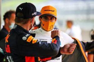 Carlos Sainz Jr., McLaren, talks to Max Verstappen, Red Bull Racing