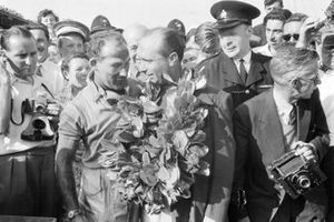 Stirling Moss gives his winner's garland to Juan Manuel Fangio