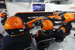 McLaren mechanics watch the race in the garage with the car of Stoffel Vandoorne, McLaren MCL32