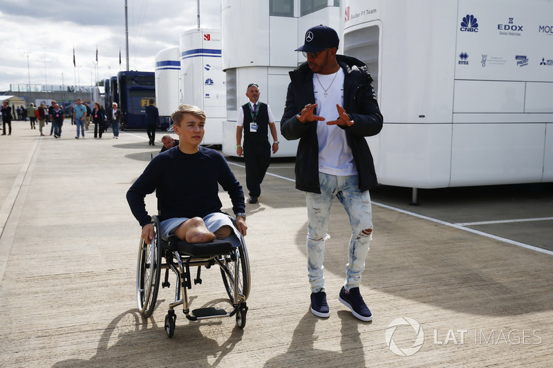 Lewis Hamilton, Mercedes AMG F1, talks to recovering British Formula 4 driver Billy Monger in the paddock
