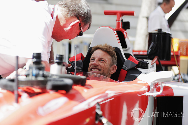 Jenson Button, McLaren, gets into the drivers seat of a 2 seat F1 demo car