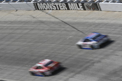 Cars race past the Monster Mile sign