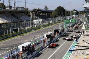 Romain Grosjean, Haas VF-20, Kevin Magnussen, Haas VF-20, and Charles Leclerc, Ferrari SF1000, leave the pits