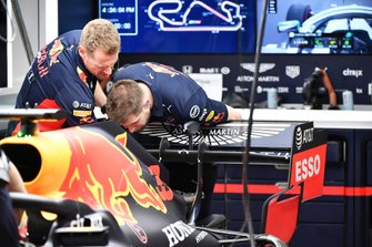Red Bull team members inspect the rear of a Red Bull Racing RB16