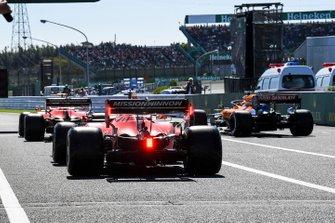 Charles Leclerc, Ferrari SF90, Carlos Sainz Jr., McLaren MCL34, et Sebastian Vettel, Ferrari SF90, dans la voie des stands