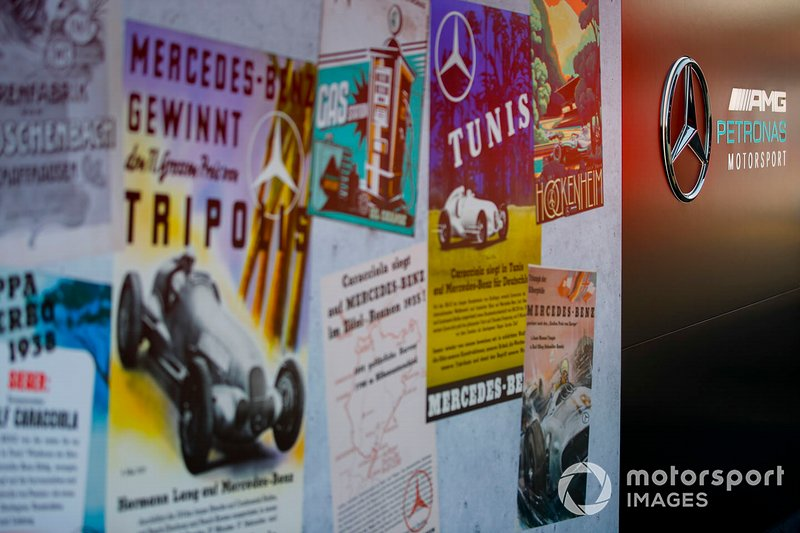 A wall of posters celebrating 125 years in motor racing for Mercedes