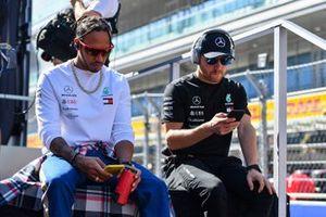 Lewis Hamilton, Mercedes AMG F1, and Valtteri Bottas, Mercedes AMG F1, look at their phones