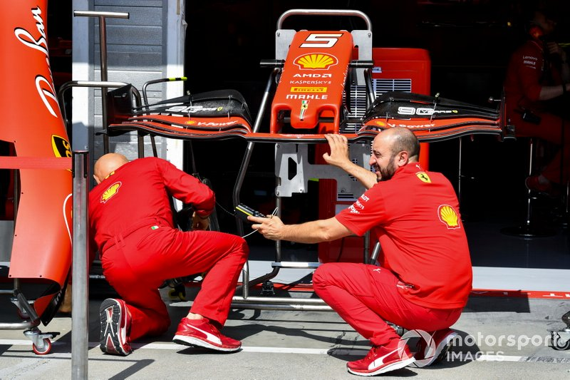 Ferrari mechanics with the front wing of Ferrari SF90
