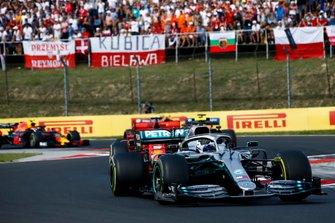 Valtteri Bottas, Mercedes AMG W10, leads Sebastian Vettel, Ferrari SF90, and Carlos Sainz Jr., McLaren MCL34