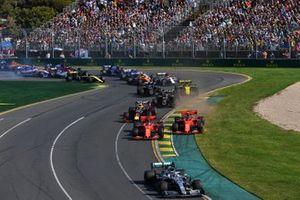 Lewis Hamilton, Mercedes AMG F1 W10, leads Sebastian Vettel, Ferrari SF90, Charles Leclerc, Ferrari SF90, Max Verstappen, Red Bull Racing RB15, Kevin Magnussen, Haas F1 Team VF-19, Romain Grosjean, Haas F1 Team VF-19, and the remainder of the field through the first corner