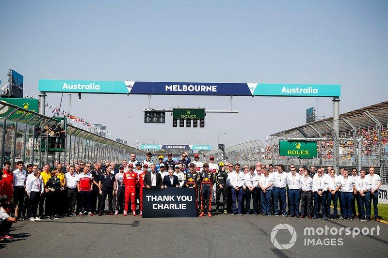 Los pilotos y el personal del equipo se reúnen detrás de Chase Carey, Presidente, Fórmula 1 y Jean Todt, Presidente, FIA, que sostienen un cartel que recuerda a Charlie Whiting.