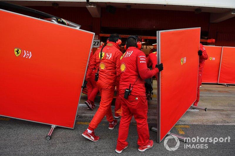 Des mécaniciens Ferrari avec des caches devant le garage