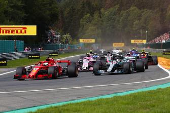 Sebastian Vettel, Ferrari SF71H, leads Lewis Hamilton, Mercedes AMG F1 W09, Esteban Ocon, Racing Point Force India VJM11, and Sergio Perez, Racing Point Force India VJM11, on the opening lap