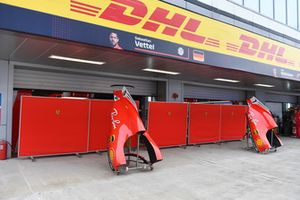 Des pièces de carrosserie de Ferrari SF71H devant les garages de l'équipe