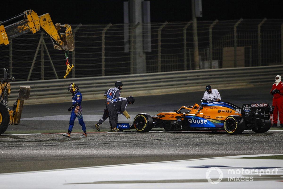 Carlos Sainz Jr., McLaren, se aleja de su coche mientras los oficiales trabajan para retirarlo