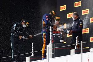 Lewis Hamilton, Mercedes, 2nd position, Lando Norris, McLaren, 3rd position, and Max Verstappen, Red Bull Racing, 1st position, celebrate on the podium