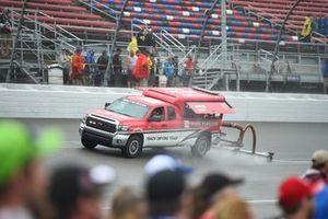 Los camiones secan la pista durante un retraso de lluvia