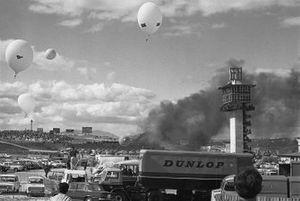 El humo se desplaza a través de la pista y el paddock después del choque de Jacky Ickx y Jackie Oliver