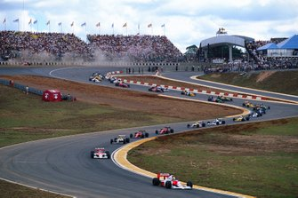 Ayrton Senna, McLaren MP4-5B Honda, in testa mentre Andrea de Cesaris, Dallara BMS-190 Ford, va fuori strada, al GP di Brasile del 1990