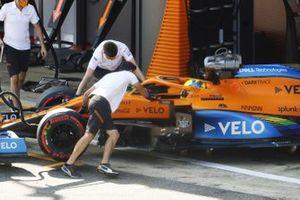 Lando Norris, McLaren MCL35, is returned to the garage