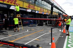 Red Bull personnel pack away their equipment in the pitlane