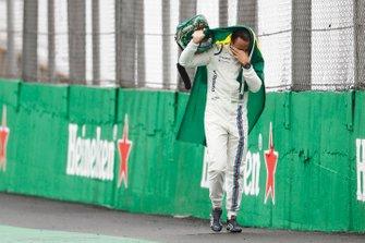 Felipe Massa, Williams Martini Racing, walks back to the garage in tears carrying a Brazilian flag afer crashing