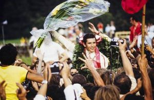 Los fans se reúnen alrededor del ganador de la carrera Jacky Ickx en la ceremonia del podio