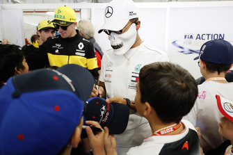 Nico Hulkenberg, Renault Sport F1 Team, and Lewis Hamilton, Mercedes AMG F1, wearing a skull mask, sign autographs for young fans