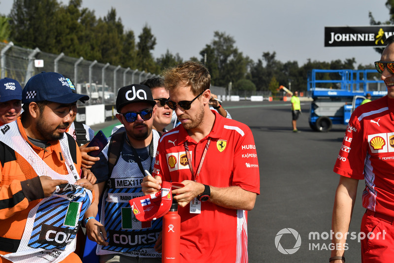 Sebastian Vettel, Ferrari signs autographs for marshals on track walk