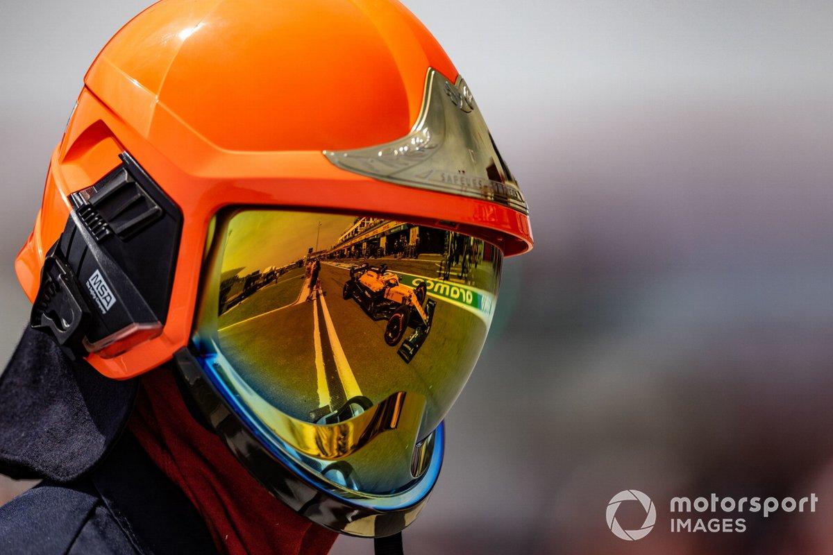 Daniel Ricciardo, McLaren MCL35M, reflejado en el casco de un comisario
