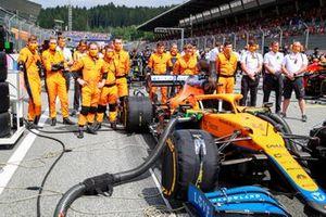 The McLaren team behind the car of Lando Norris, McLaren MCL35M, on the grid