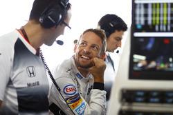 Jenson Button, McLaren habla con ingenieros en el garaje