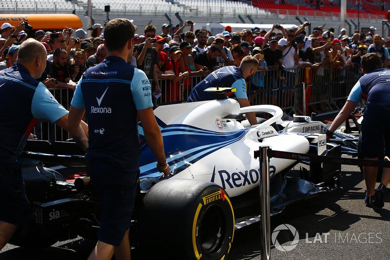 Des mécaniciens de Williams poussent la voiture de Sergey Sirotkin Williams FW41 devant des fans