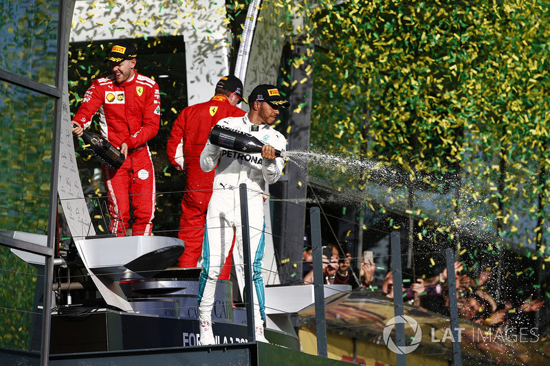 Lewis Hamilton, Mercedes AMG F1, 2nd position, Sebastian Vettel, Ferrari, 1st position, and Kimi Raikkonen, Ferrari, 3rd position, celebrate on the podium with Champagne