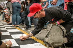 Fans sign the Start-finish-line