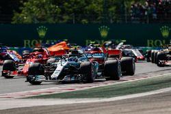 Valtteri Bottas, Mercedes AMG F1 W09, voor Kimi Raikkonen, Ferrari SF71H, Sebastian Vettel, Ferrari SF71H, en de rest bij de start