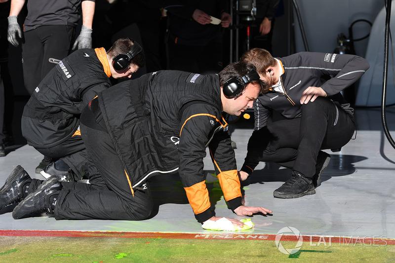Механики McLaren счищают специальную краску с пола гаража